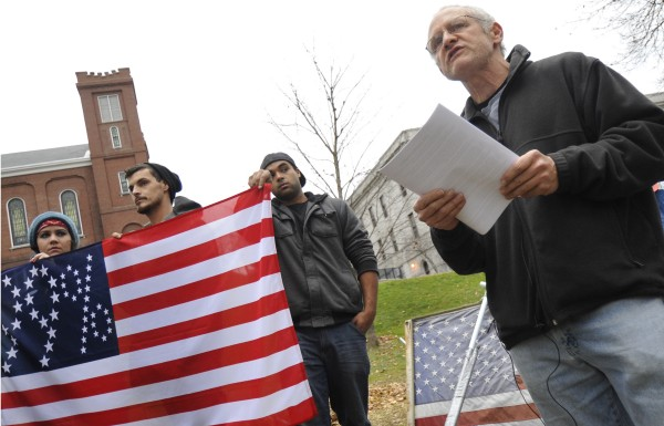 Occupy Bangor member Lawrence Reichard (right) addresses the media during a press conference at Peirce Park on Sunday afternoon, Nov. 20, 2011. Holding up the group's 99% flag behind Reichard are (from left) Rebecca Hickman, Jeffrey F. Joseph and Matt Murray.
