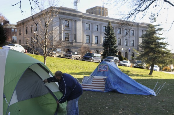 Jim Frye of Bangor closes the tie-back door on a tent that was erected Sunday, Nov. 20, 2011, and that he and others slept in overnight. He said he and other Occupy Bangor participants held a gathering at Peirce Park into the early hours of  Monday morning.