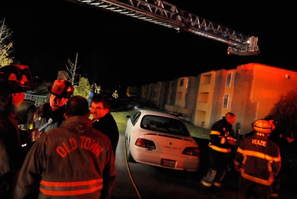 Orono, Old Town and Veazie firefighters compare notes in the aftermath of a fire at Stillwater Village Apartments off College Avenue in Orono Saturday evening, Nov. 19, 2011. A section of College Avenue in front of the apartment complex was closed to traffic for more than two hours as the firefighters contained the fire, which spread from the back basement to the third floor of part of the complex.