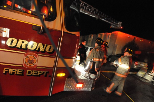 Orono, Old Town and Veazie firefighters gather near a ladder truck in the aftermath of a fire at Stillwater Village Apartments off College Avenue in Orono Saturday evening, Nov 19, 2011.