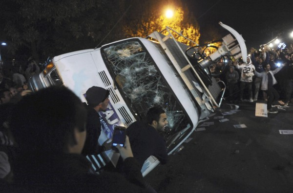 Penn State students flip a television news van during a riot after it was announced that Joe Paterno would no longer be head coach of Penn State Football.