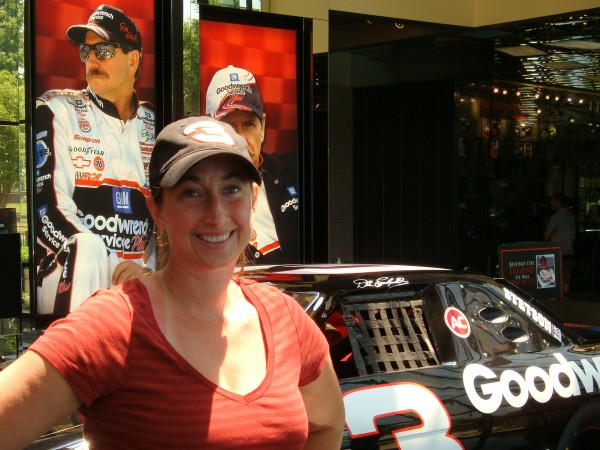 University of New England Assistant Prof. Lara Carlson is seeking to conduct breakthrough research on the physiological stresses faced by stock car drivers. Carlson is seen here posing with the black No. 3 Goodwrench car of the late NASCAR star Dale Earnhardt Sr.