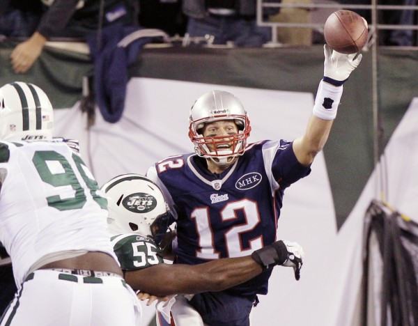 New England Patriots' Tom Brady (12) tries to throw the ball away and is called for a safety as he is pressured by New York Jets outside linebacker Jamaal Westerman (55) during the second quarter of an NFL football game Sunday, Nov. 13, 2011 in East Rutherford, N.J.
