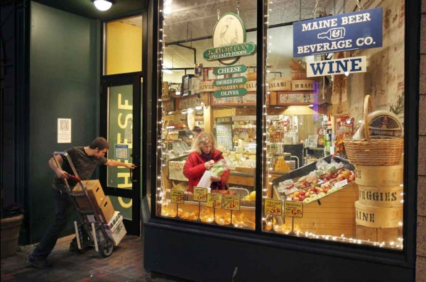 A shopper picks produce while a delivery arrives in the evening at Public Market House in Portland.