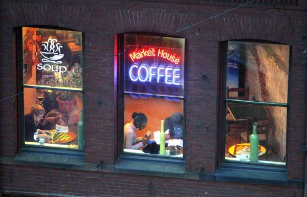 A neon sign glows in the evening near the coffee shop on the second floor of the Public Market House in Portland.