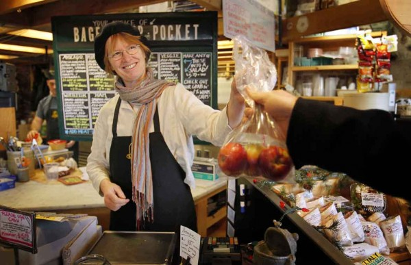 Kris Horton sells apples to a customers at her gourmet food shop at the Public Market House in Portland.