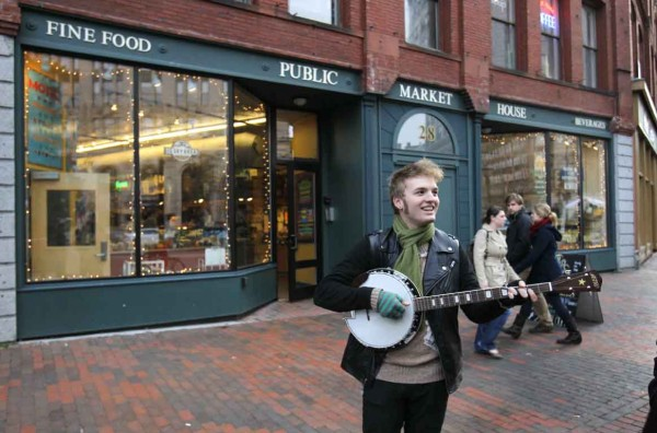 Cormac Brown of Portland strums his new banjo in front of the Public Market House in Monument Square.