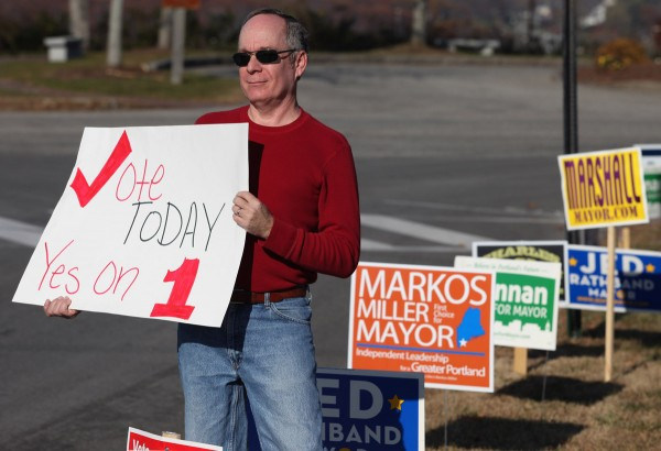 Matt Berk, of South Portland, holds a sign in support of Question 1, Tuesday, Nov. 8, 2011, outside of the polls at the East End School in Portland, Maine.