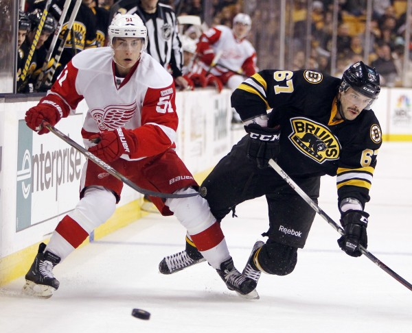 Boston Bruins' Benoit Pouliot (67) falls while battling Detroit Red Wings' Valtteri Filppula (51) for the puck in the third period of an NHL hockey game in Boston on Friday, Nov. 25, 2011. The Red Wings won 3-2 in a shootout.