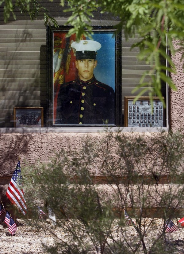 A portrait of Marine Jose Guerena Ortiz is shown in the window of his home Tucson, Ariz., on June 9, 2011. Guerena was shot and killed on May 5, 2011 by the Pima County Sheriff's Department. The Sheriff's Department said its SWAT team was at the home because they suspected Guerena of being involved in a drug-trafficking organization that specialized in ripping off smugglers. The SWAT team fired 71 times, riddling Guerena 22 times, while his wife and child cowered in a closet.