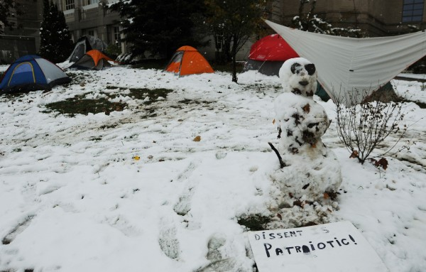 A lone snowman stands vigil next to tents on the lawn at the Bangor Public Library on Sunday, October 30, 2011.