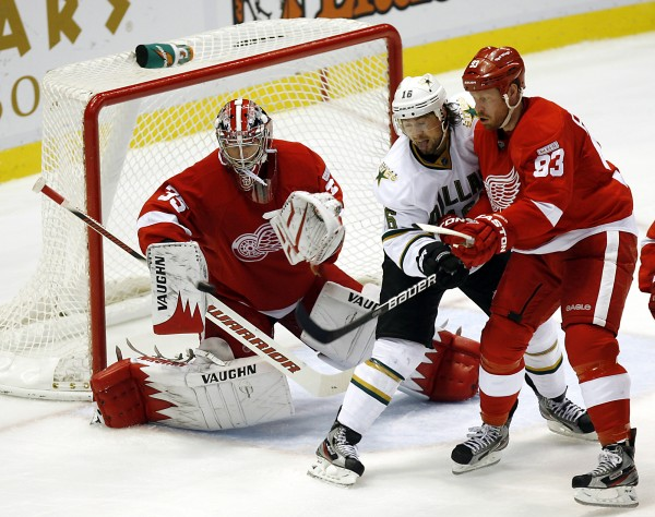 Detroit Red Wings goalie Jimmy Howard (35) stops a shot on goal as Dallas Stars' Adam Burish (16) and Red Wings' Johan Franzen (93), of Sweden, fight for position during the second period of an NHL hockey game, Saturday, Nov. 12, 2011, in Detroit.