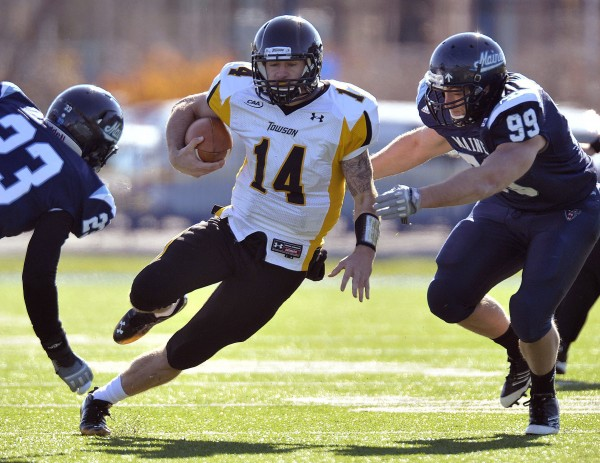 Towson quarterback Grant Enders (14) scrambles for yardage and is brought down by Maine's Troy Russell (23) and Michael Cole (99) during the first half of an NCAA football game in Orono on Saturday, Nov. 5, 2011.