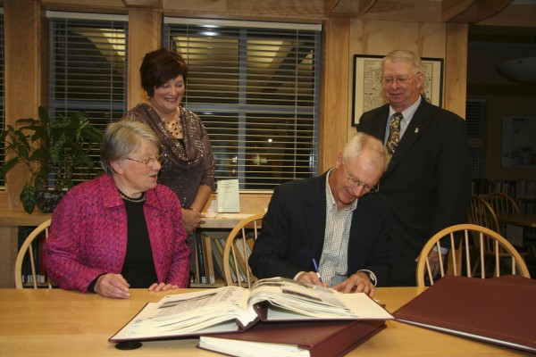 Holly and Dennis Violette (seated) sign documents donating a 25-volume set of scrapbooks, compiled by Marcella Belanger Violette, to the University of Maine at Fort Kent''s Acadian Archives/Archives Acadiennes. Looking on are (standing left) Lise Pelletier, director of the archives, and Wilson G. Hess, UMFK president.