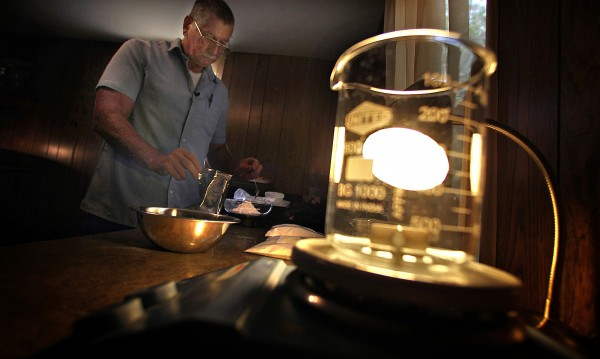 Light shines through a beaker in the mobile home that Rodger Seratt, of Fairdealing, Miss., used to house the laboratory where he mixes synthetic drugs that include bath salts and herbal incense, August 11, 2011.