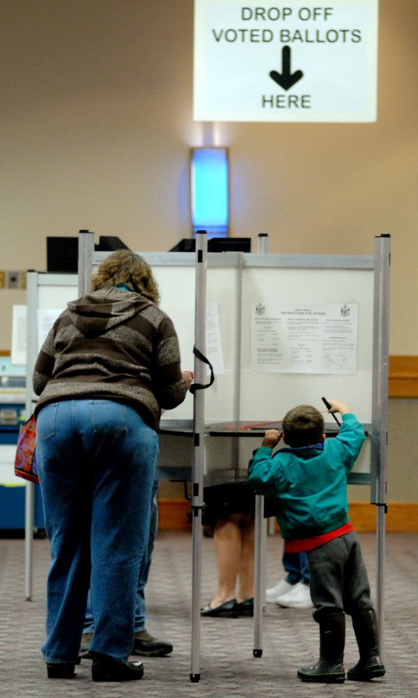 Mason King, 3, appears to be casting his own vote while he waiting for his mother Marjorie King (left) at the Bangor Civic Center Tuesday morning.