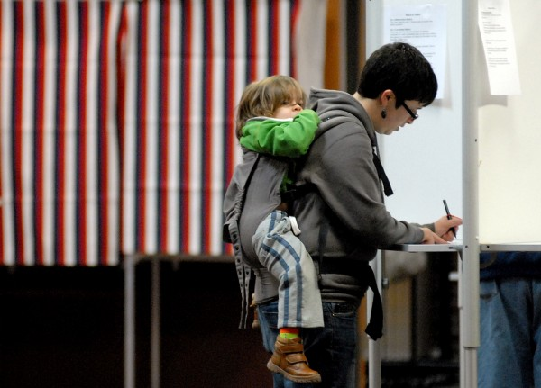 Ruth Clark visits the polls at the Bangor Civic Center Tuesday morning to cast her vote with son Linus, 2, enjoying the ride.