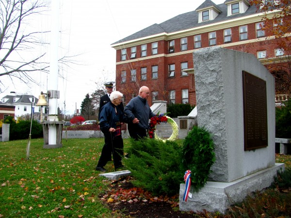 Carl Rand (right) escorts Noreen Robinson on Friday, Nov. 11, 2011, as they lay a wreath at a memorial in Castine for merchant mariners and members of the U.S. Naval Armed Guard killed in World War II. The memorial, which is located on the campus of Maine Maritime Academy, was donated by members of the Down East chapter of the organization American Merchant Marine Veterans.