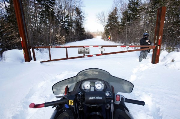 A snowmobile is parked outside a gate on land owned by Roxanne Quimby in January 2011.