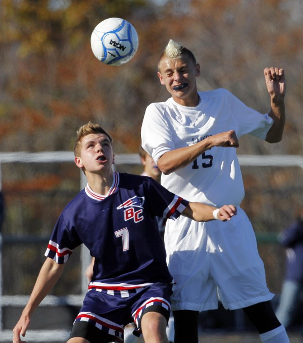 Bangor Christian's Rem Poulin (left) and Greenville's Matthew DiAngelo jump for a midfield pass in the Class D soccer state championship in Falmouth on Saturday, Nov. 5, 2011.