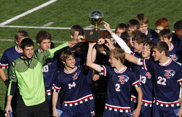 Bangor Christian's Brad Wilcox (14) and Seth Pearson (2) lead the Patriots after receiving the trophy for winning the Class D soccer state championship victory over Greenville in Falmouth on Saturday, Nov. 5, 2011.