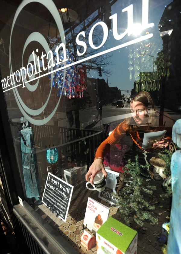 Cara Oleksyak, an assistant at Metropolitan Soul in downtown Bangor, arranges the window display on Tuesday, Nov. 22, 2011. While the mall's big box stores will be flooded with Black Friday shoppers many people will visit smaller shops like Metroplitan Soul to find unique items for gifts.