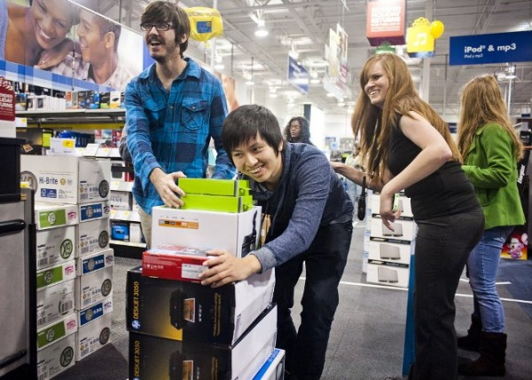 Shelby Buquet and Phi Nguyen push their items towards a cash register at Best Buy early Friday, in Houma, La. They were among the first to shop there on Black Friday.