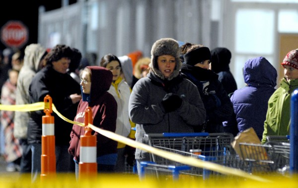 Customers stand in long lines outside of the Brewer Walmart on Thursday waiting for the doors to open at midnight on Black Friday.