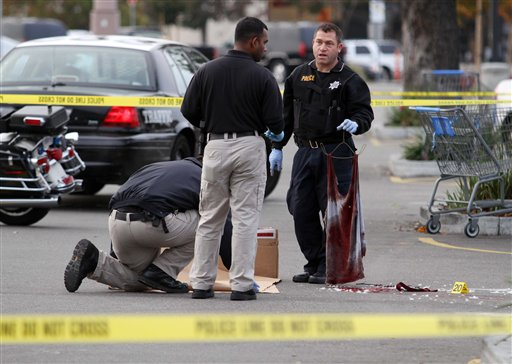 A San Leandro police officer, right, holds a bloody shirt as evidence is gathered at the scene of a shooting at Wal-Mart on Hesperian Boulevard, Friday, Nov. 25, 2011, in San Leandro, Calif.