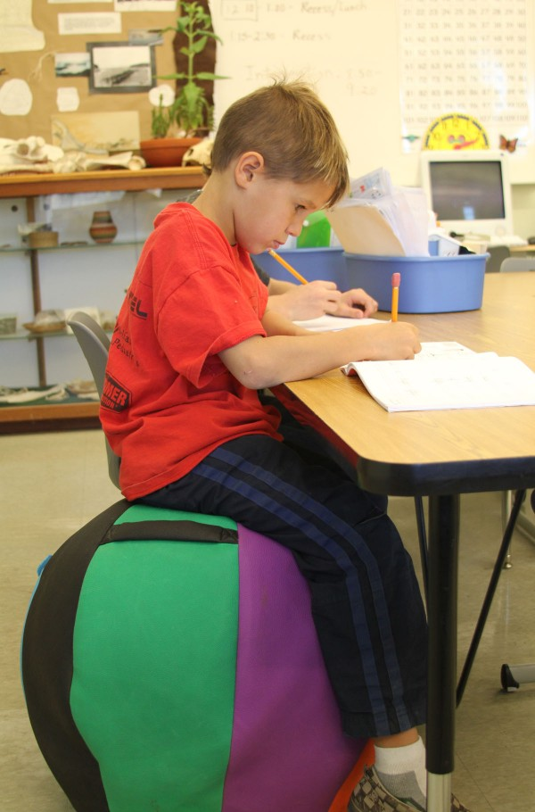 Cameron Hedstrom, 8, of Camden, practices writing the letter &quotI&quot in cursive while sitting on a bouncy ball. The ball is one tool in the Camden-Rockport Elementary School's third-grade boys-only class that helps students focus.