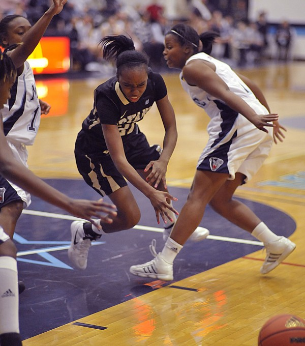 Bryant guard Danielle Douglas (21) gets stripped of the ball between Maine's Amber Dillon (12) and Ashleigh Roberts (1) in the second half of their game in Orono, Saturday Nov. 19, 2011. Bryant won 65-53.