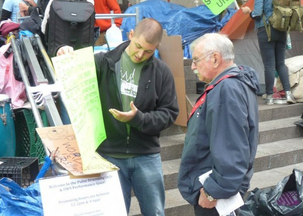 Chace Jackson (left) discusses economic and social issues with an interested citizen last month in Zuccotti Park. Jackson was visiting his cousin Earnie Gardner in New York City and made it a point to take part in the ongoing Occupy Wall Street movement. Both Jackson and Gardner are from Allagash.