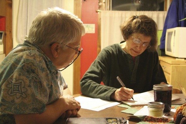 Sally Perkins (left) and Nancy Glassman look over paperwork about how to make a home more energy-efficient. Perkins received a free energy audit in her Warren home on Wednesday.