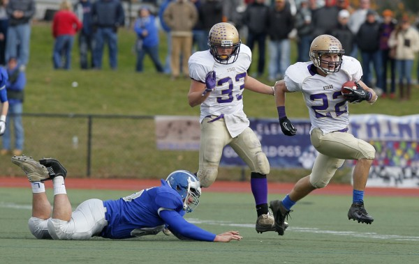 Cheverus' Donald Goodrich leaves Lawrence defender Roy Barnaby on the ground as he returns a kick off 90m yards for his third touchdown of the half during the Class A state championship football game, Saturday, Nov. 19, 2011, at Fitzpatrick Stadium in Portland.