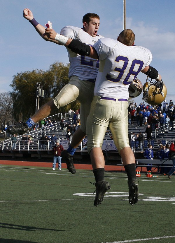 Cheverus running back Donald Goodrich, left, chest-bumps with teammate Lucas Richio after defeating Lawrence to win the Class A state championship football game, Saturday, Nov. 19, 2011, at Fitzpatrick Stadium in Portland.