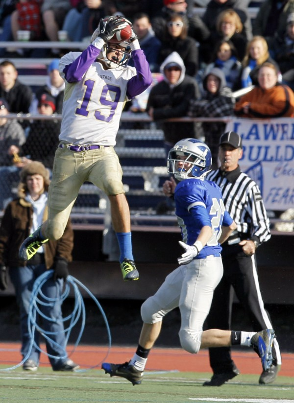 Chevrus' Louis DiStasio intercepts a Alex Leather's pass in front of Lawrence's Aaron Lafrance during the third quarter of the Class A state championship football game, Saturday, Nov. 19, 2011, at Fitzpatrick Stadium in Portland.