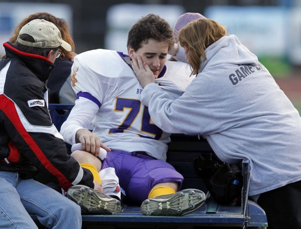 Bucksport's Cody Gray is consoled by Kay Russell as he leaves the field with a probable torn ACL against Yarmouth in the Class C state championship football game, Saturday, Nov. 19, 2011, at Fitzpatrick Stadium in Portland. The injury is doubly tough for Gray, who is also playing the lead role in the school's production of &quotFootloose.&quot