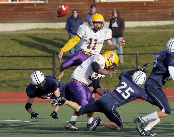 Bucksport's Mike Cummings has his punt blocked by Yarmouth defenders in the first quarter in the Class C state championship football game, Saturday, Nov. 19, 2011, at Fitzpatrick Stadium in Portland.