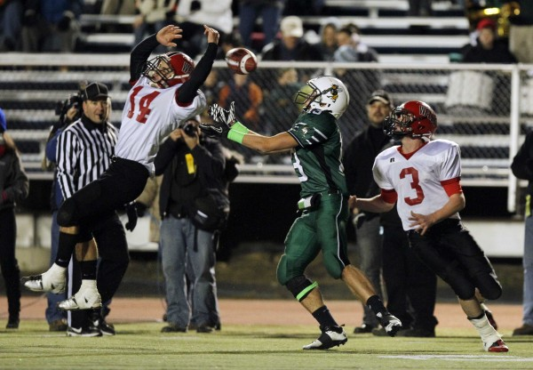 Leavitt's Brian Bedard, center, has a pass broken up by Wells defenders Gavin Snapp, left, and Paul McDonough during the Class B state championship football game, Saturday, Nov. 19, 2011, at Fitzpatrick Stadium in Portland.