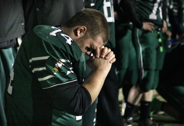 Leavitt's Josh Allaire says a prayer on the sideline while his team makes their final drive in thier loss to Wells in the Class B state championship football game, Saturday, Nov. 19, 2011, at Fitzpatrick Stadium in Portland.