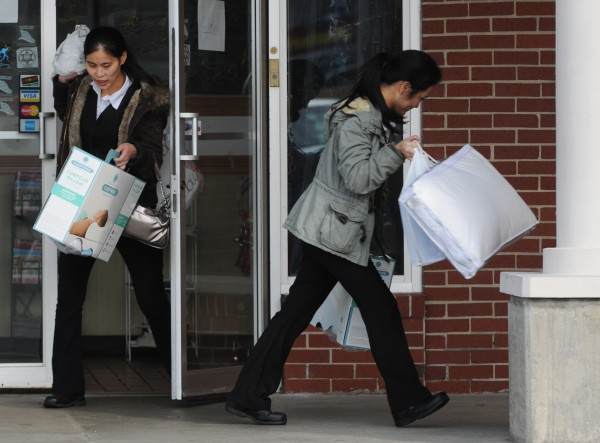 Women run from the Twin Super Buffet in Brewer on Wednesday, November 16, 2011. Federal agents were seen removing boxes earlier.