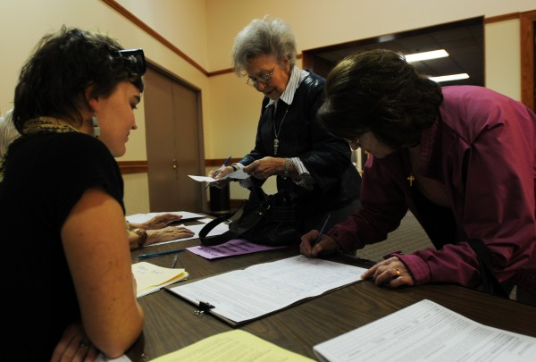 Abbie Strout (left), a volunteer with EqualityMaine watches as voters leaving the polls at the Bangor Civic Center sign a petition to bring the gay marriage question to voters again next year during the November elections.