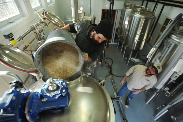 Andy Geaghan pours the last of almost 400 pounds of grain into the mash tun at Geaghan Brothers Brewing Co. in Geaghan's Pub in Bangor on Monday, Nov. 21, 2011, as brew master Jason Courtney watches.