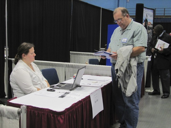 Brian Campbell of Norridgewock, an Army veteran, talks with Amie Parker, the employment manager at Bates College in Lewiston, during a Hiring our Heroes job fair Thursday, November 10, 2011, at the Augusta Civic Center. Campbell said that after decades as a landscape architect, he's looking for a job that will keep him inside during the winter months.