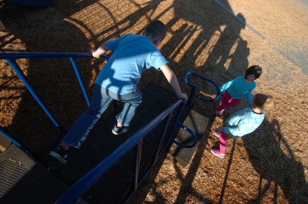 Leroy H. Smith School first-grader Brent Gardner, 6, jumps off a playscape to surprise first-graders Emma Roy, 6, and Peyton Spahr (right), 6.