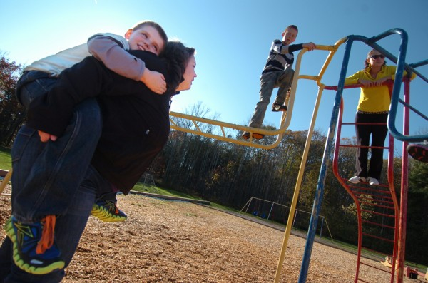 Leroy H. Smith School fourth-grader Dominic Coolidge, 9, piggybacks on Maggie Mourkas, a teacher with Bangor's Y-Works during Y-Works after-school program at the school Wednesday, Nov. 2, 2011. Behind them on the school's playscape are Alex Roy, 9 and  Jenny Hill, a Y-Works childcare coordinator at the school.