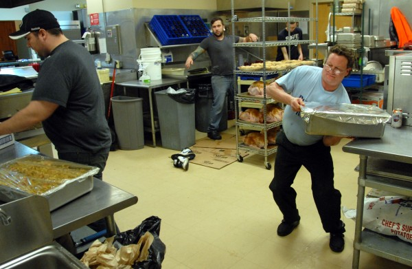 Gillmor's Restaurant cook Fred Kaplan (far right) hoists a heavy tray of stuffing as manager and head chef Cole Averill wraps another stuffing tray as the Lincoln eatery's kitchen staff prepares Wednesday for a free Thanksgiving Day dinner it will offer on Thursday, Nov. 23, 2011.