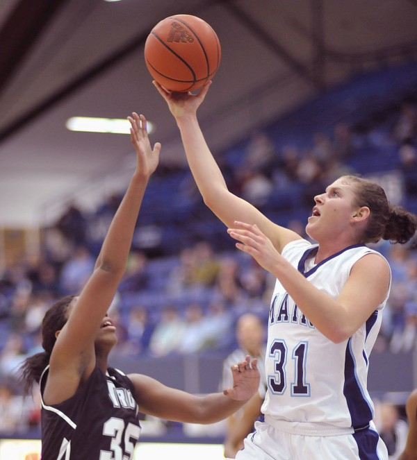 Maine guard Rebecca Knight (21) drives for two points past Troy forward Kourtney Coleman (35) in the second half of their game in Orono on Friday, Nov. 25, 2011.