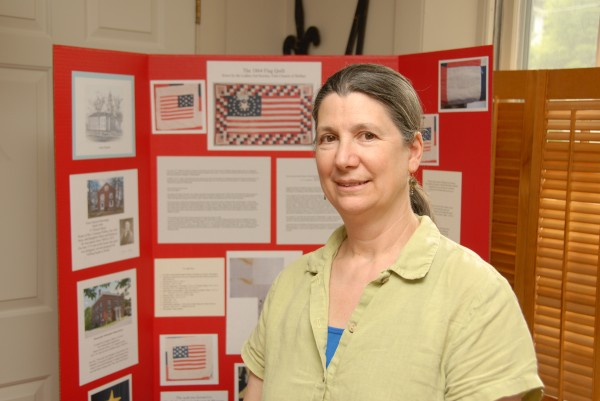 Megan Pinette is curator of the Belfast Historical Society and Museum. Behind her is a display about the 1864 Flag Quilt, also known as a Civil War soldiers' quilt.
