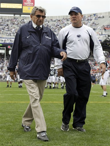 Penn State coach Joe Paterno, left, walks with assistant coach Tom Bradley on the field before an NCAA college football game against Syracuse in State College, Pa. in 2009.
